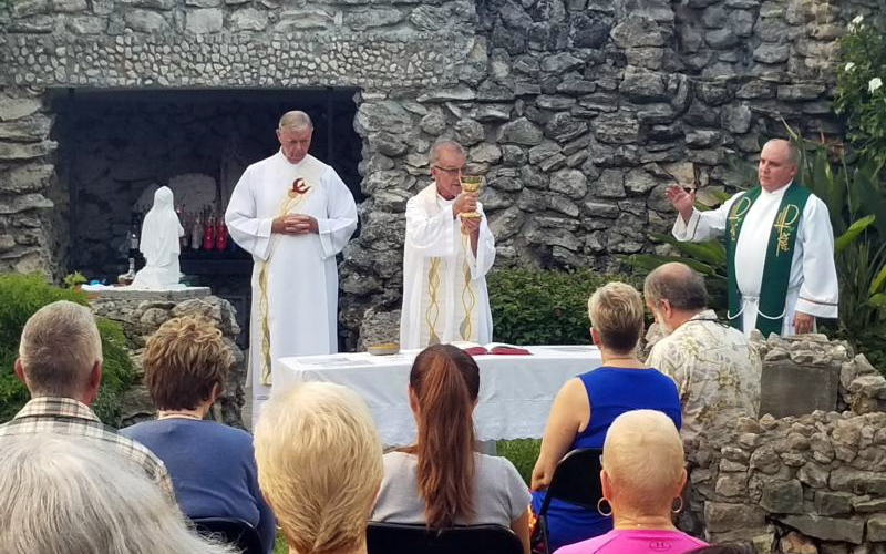 Father John Baker, pastor of the Basilica of St. Mary Star of the Sea in Key West, Fla., celebrates an early morning Mass Sept. 7 at the basilica's grotto with special prayers for safety before Hurricane Irma. At left, is Deacon Peter Batty and at right is Father Juan Rumin Dominguez, both from the basilica.
