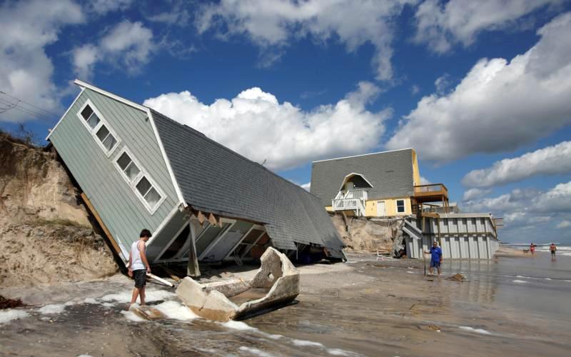 Residents look at a collapsed house Sept. 12 after Hurricane Irma passed the area in Vilano Beach, Florida.