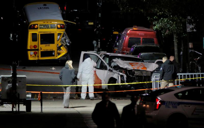 "Police investigate the crime scene early Nov. 1 after a man driving a rented pickup truck ran down pedestrians and cyclists on a bike path alongside the Hudson River in New York City. The incident occurred near the World Trade Center memorial, killing at least eight and seriously injuring 11 in what the Mayor Bill de Blasio called ""a particularly cowardly act of terror."" (CNS photo by Andrew Kelly/Reuters)"