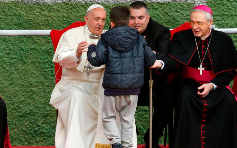 Pope Francis embraces Emanuele, a boy whose father died, as he visits St. Paul of the Cross Parish in Rome April 15. (CNS photo by Paul Haring)