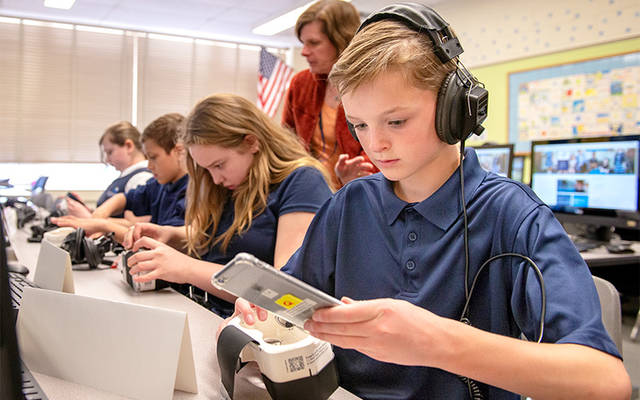 <p>Fifth-grader Dane Lewis loads an iPhone into virtual reality goggles before a lesson May 1 at Pittsford's St. Louis School. (Courier photo by Jeff Witherow)  </p>