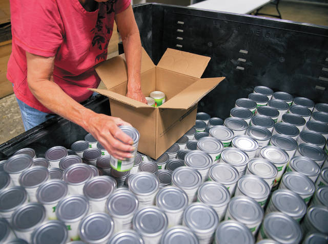 Volunteer Connie Breed sorts canned good items for the backpack program  at the Food Bank of the Southern Tier on July 20.
