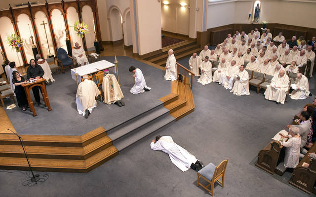 <p>Father Kevin Mannara prostrates in front of the altar during his ordination Aug. 5.