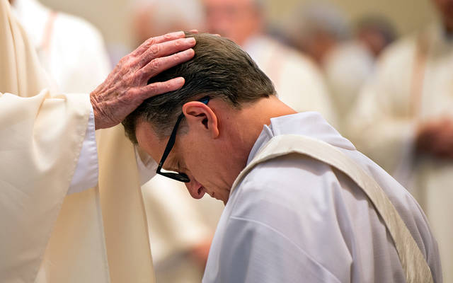 <p>Priests lay their hands on Father Kevin Mannara's head during his ordination Aug. 5.