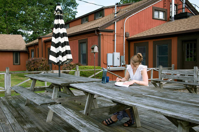 <p>Mariana Mazzarolo of Toronto, Canada, reads on the deck of Bethlehem Retreat House at the Abbey of the Genesee in Piffard Aug. 4. </p>