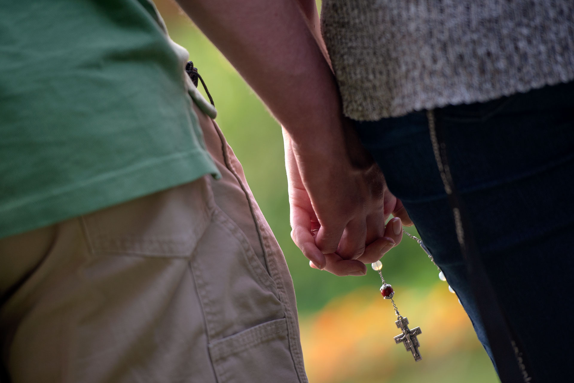 """A couple holds hands while praying the rosary during the """"Grilling with God"""" young-adult event at Rochester's St. John the Evangelist Church Aug. 15. (Courier photo by Jeff Witherow)"""