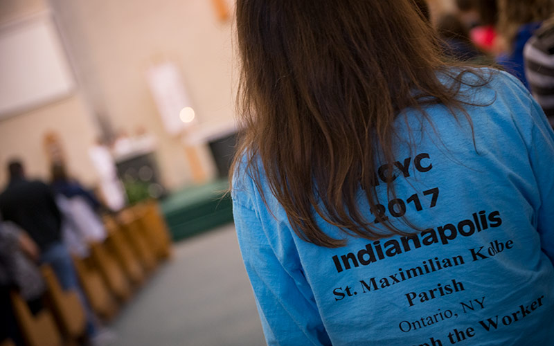 A participant in the Oct. 29 Mass wears a shirt in support of the upcoming trip to Indianapolis for the National Catholic Youth Conference.