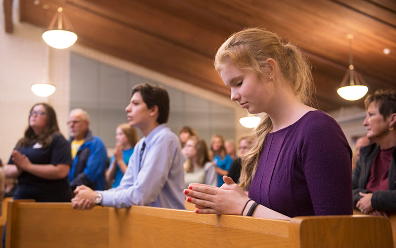 Helen Rose Shine kneels in prayer during a Mass for National Catholic Youth Conference pilgrims Oct. 29.