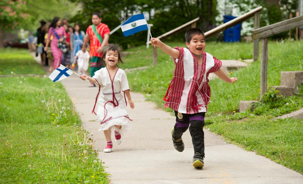 Eight-year-old Sat Soe (right) and 5-year-old Nee Tse run with flags.