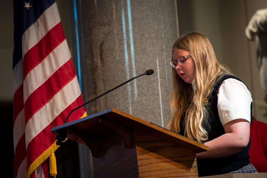 St. Mary School eighth-grader Rebecca Steinmetz reads names of some of the service members who are being honored.