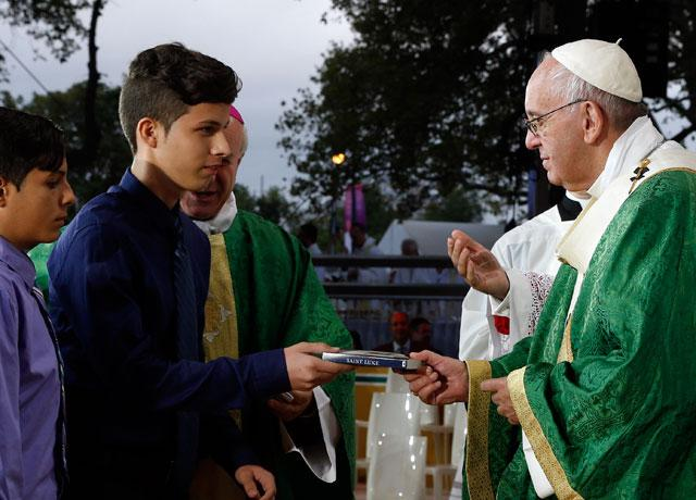 Pope Francis presents copy of Gospel of Luke to young man during closing Mass of World Meeting of Families