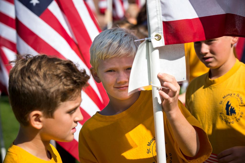 A St. Mary School student reads one of the cards attached to a flag.<br />