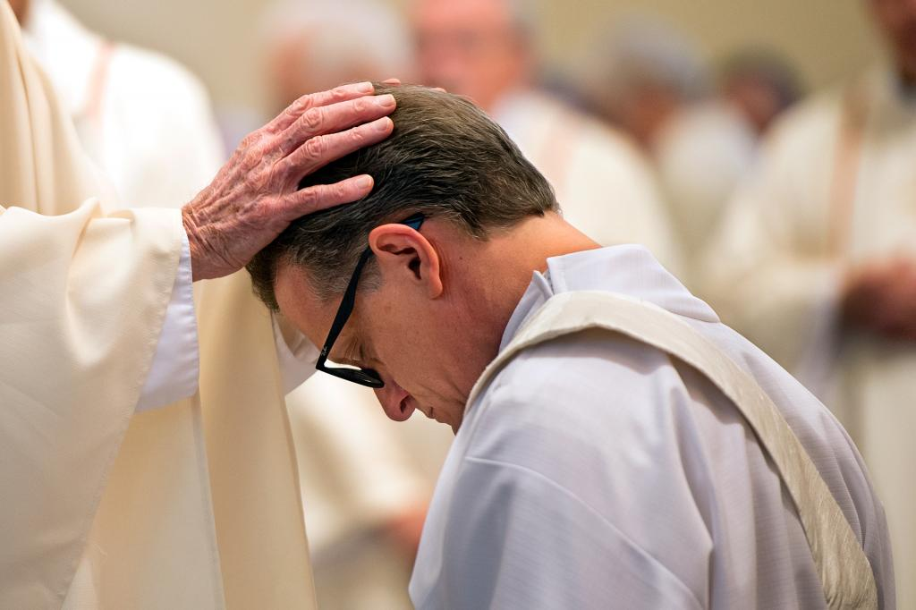 Priests lay their hands on the head of Father Kevin Mannara during the ordination Mass.