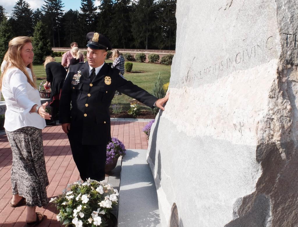 Francis Camp of the Rochester Police Department talks with stone carver Karin Sprague following the dedication of the First Responders section and monument at Holy Sepulchre Cemetery in Rochester Sept. 9.