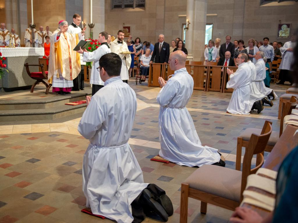 The five newly ordained deacons kneel before the altar.