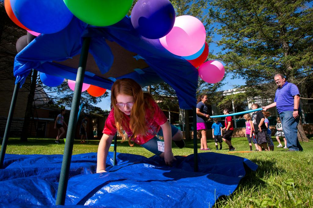 Catelyn Yunits crawls through an obstacle course July 19 during vacation Bible school at St. Francis and St. Clare Parish in Waterloo.