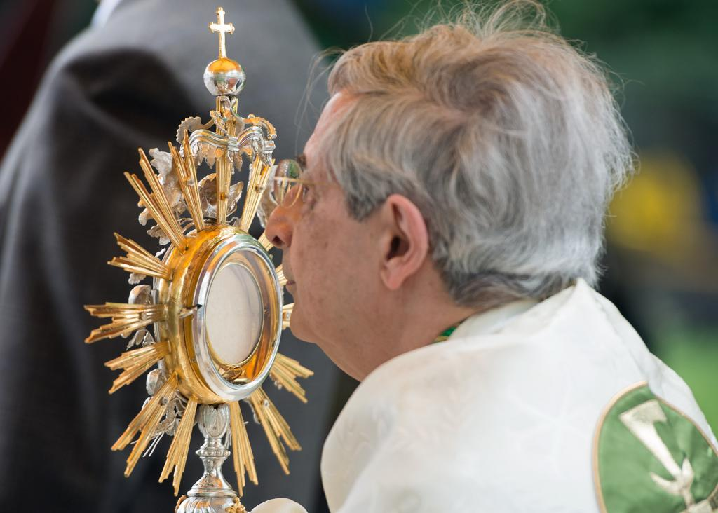Bishop Matano processes with the Blessed Sacrament toward the third altar.