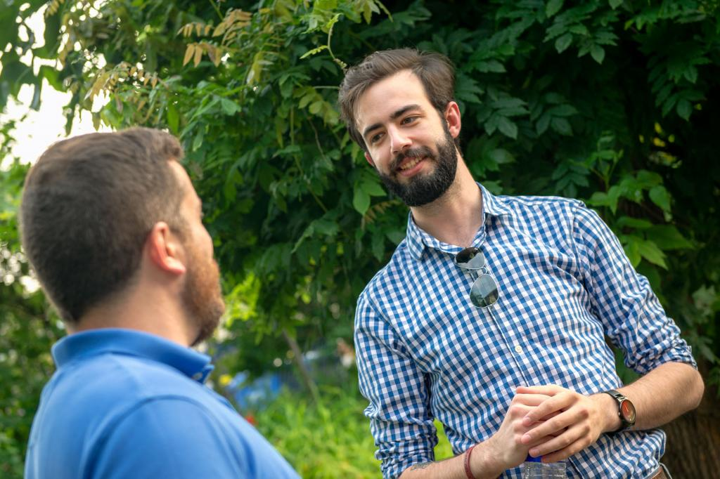 John Morasse (right) and Brian Murphy speak in the Fr. Edward Zimmer Memorial Garden outside the church.
