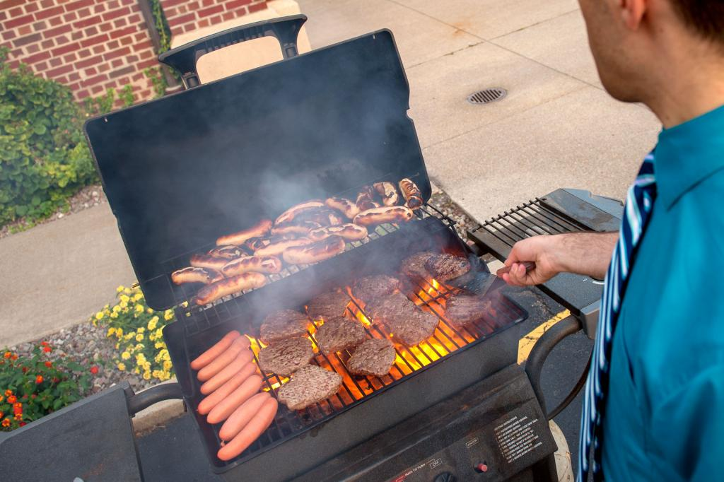 Burgers and hot dogs are prepared during the cookout.