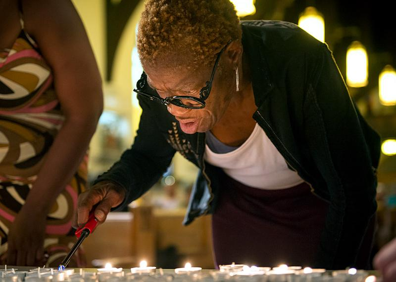 During a June 15 memorial service for the homeless at Rochester's Our Lady of the Americas Church, Kathleen Federico lights a candle in memory of a homeless person who had passed away.
