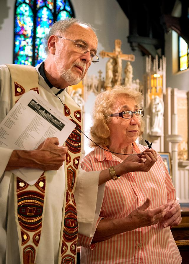 Father Robert Werth holds a microphone for Sister Grace Miller of the House of Mercy while she shares some remarks.