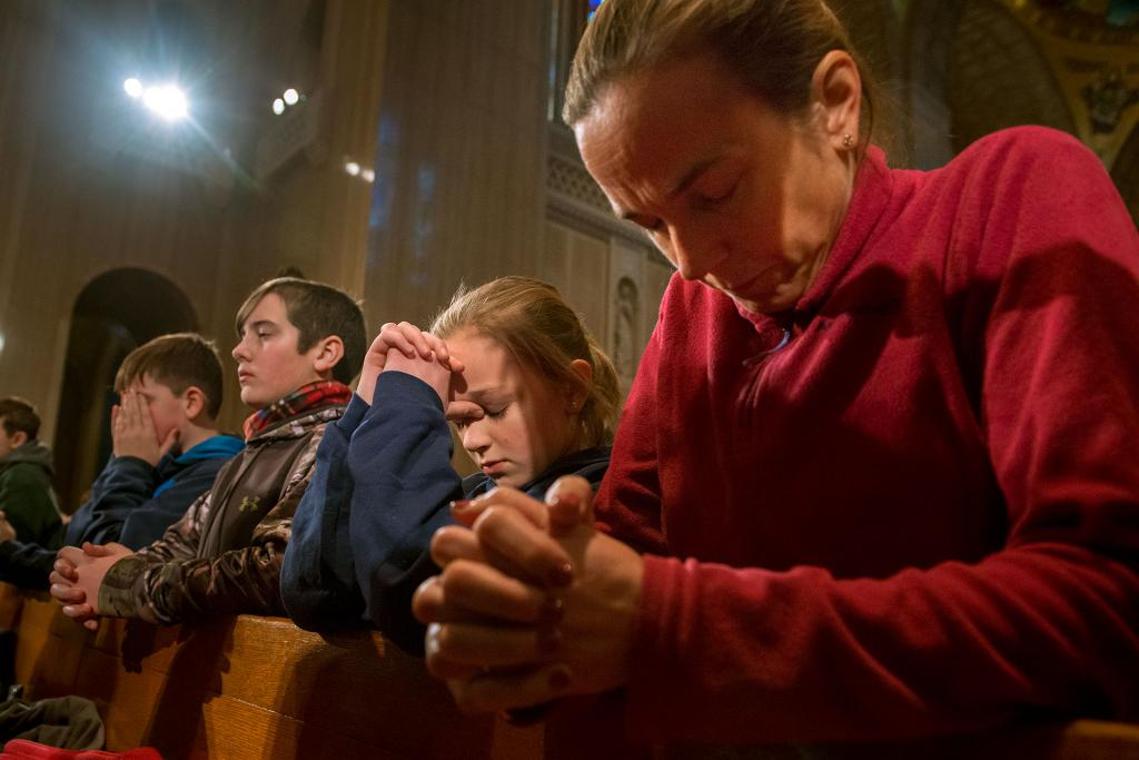 Eleven-year-old Sarah Lawson of Addison (left) and her mother, Julie Lawson (right), kneelduring Mass.