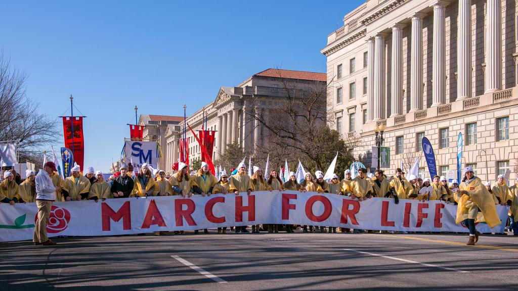 March attendees carry a banner at the front of the procession.