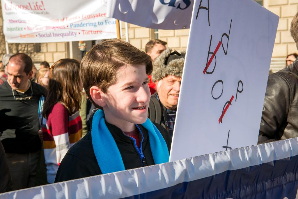 Thirteen-year-old Seth Edwards of Spencerport walks behind the Diocese of Rochester banner during the march.