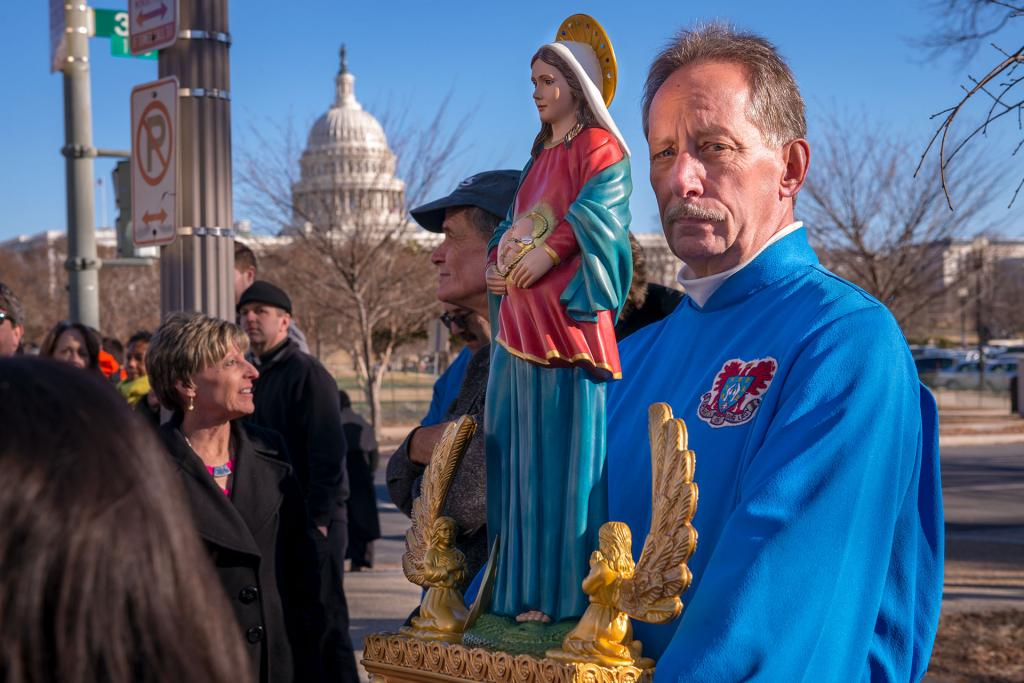 A Knights of Our Lady member holds a statue of Mary near the U.S. Capitol building.