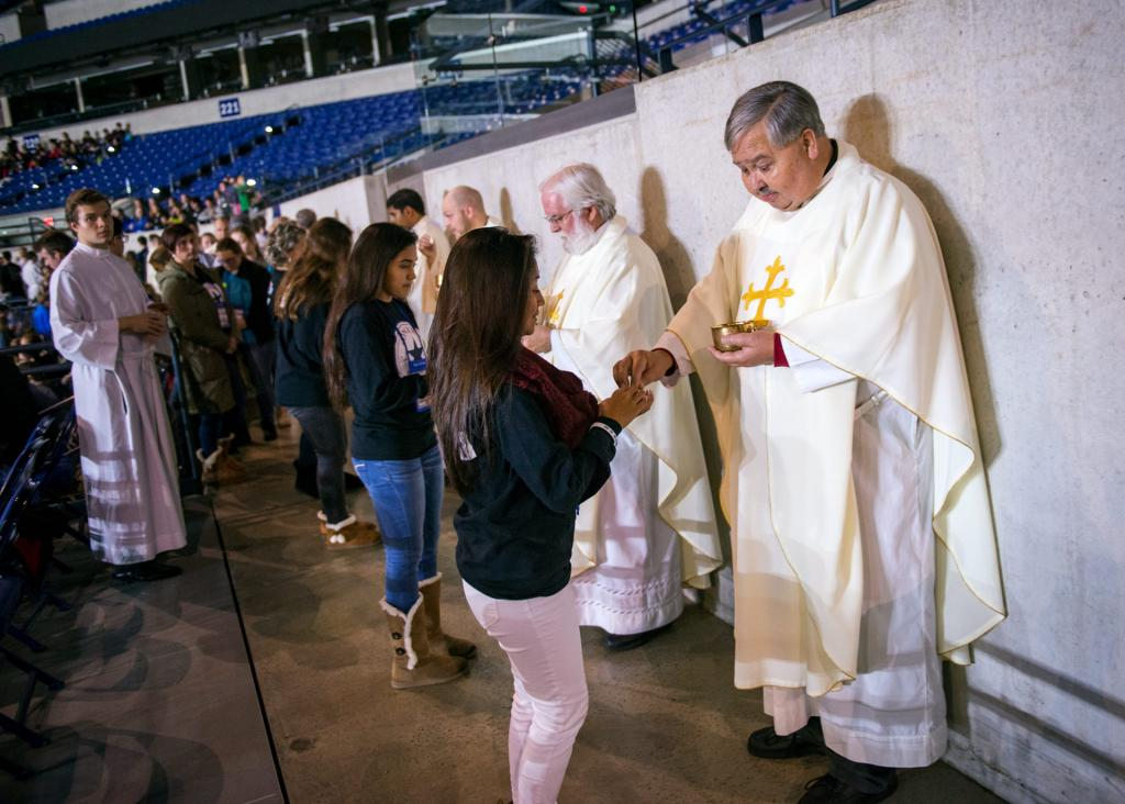 Father Michael Schramel distributes Communion during Mass at Lucas Oil Stadium Nov. 18.