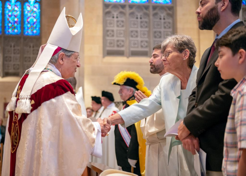 Bishop Salvatore R. Matano greets Elaine Chichester, mother of the ordinand, during the procession.