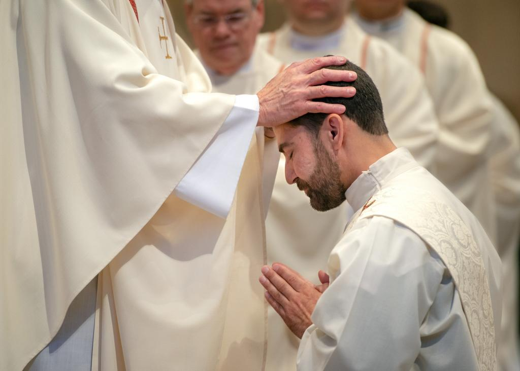 Diocesan priests placetheir hands on the head of Father Jeffrey Chichester.