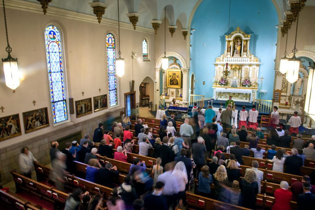 Congregants stand to receive Communion.