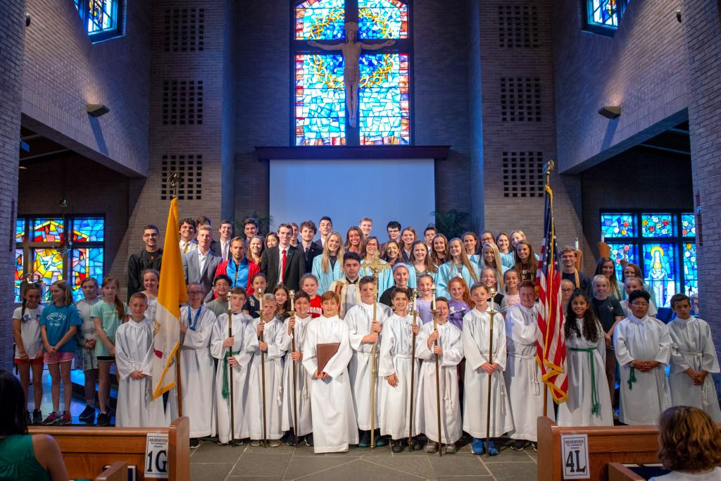 Alumni of St. Louis School in Pittsford who are graduating from high school this year pose with St. Louis fifth-graders and Father Juan Benitez during a prayer service June 20.