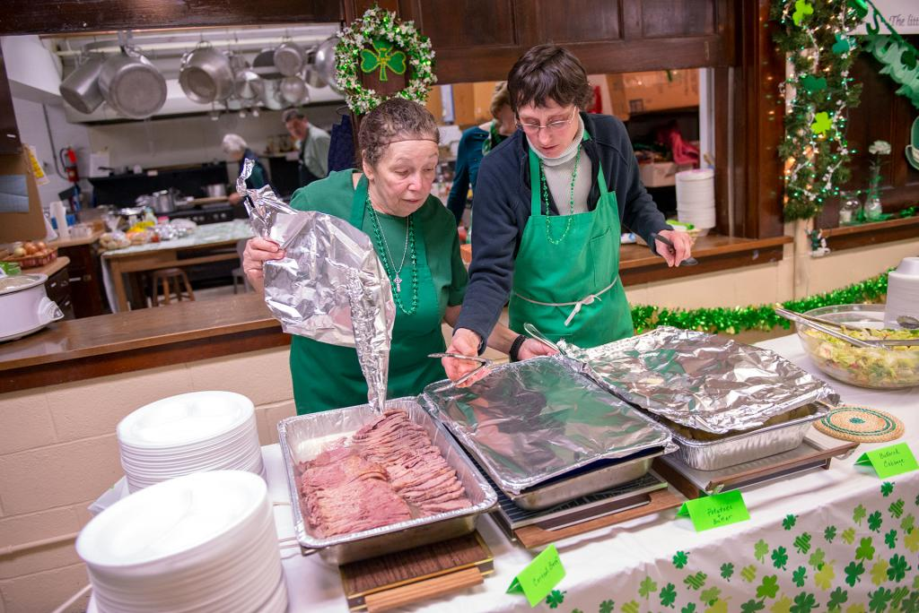 Lorraine Hoffman (left) and Arlene Farmer set out the corned beef at the start of dinner. (Courier photo by Jeff Witherow)