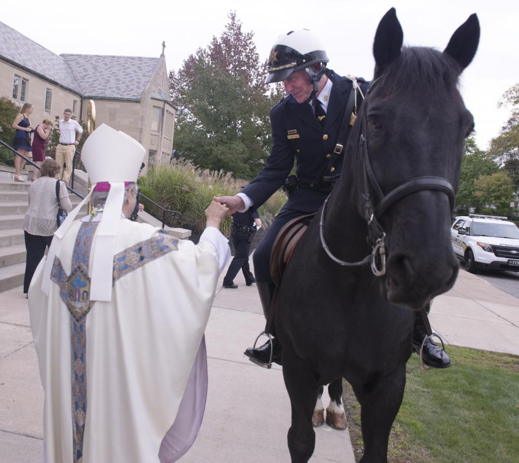 Bishop Salvatore R. Matano greets a mounted police officer following the Blue Mass at Sacred Heart Cathedral Oct. 14.
