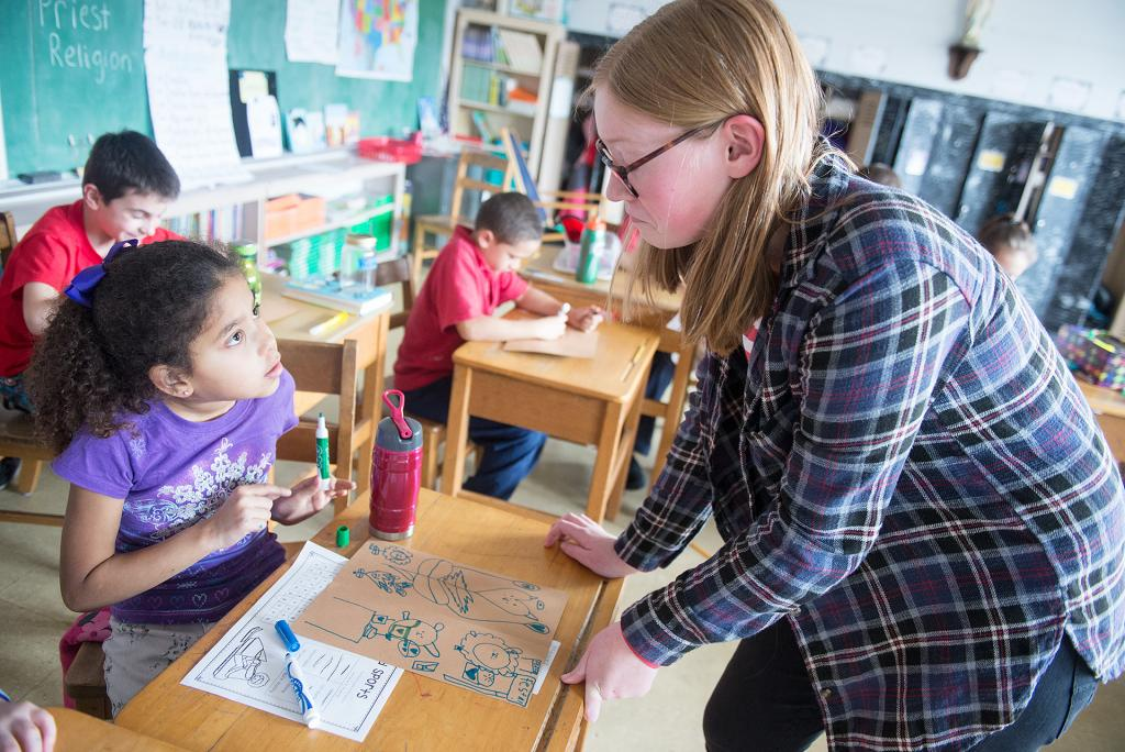 """Kiya Borin, a third-grader at St. Francis-St. Stephen School in Geneva, asks a question of eighth-grader Sally Young, who was teaching Kiya's class as part of """"Switch Day"""" Jan. 29."""
