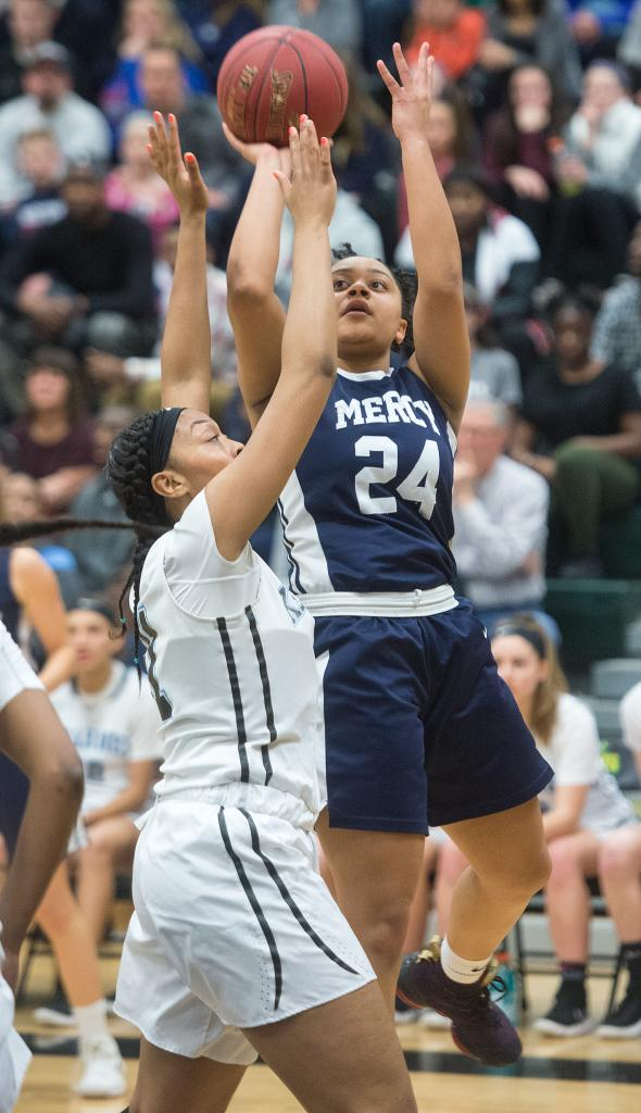 Mercy's Traiva Breedlove (24) puts up a shot for two as a Bishop Kearney player defends in the first quarter of the Section 5 Class AA sectional championship game March 3. (Courier Photo by John Haeger)
