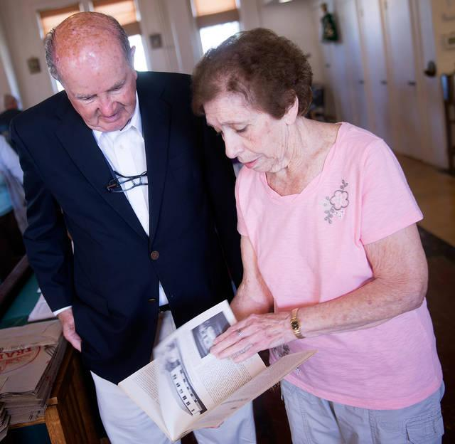 <p>Rose Giovine and Gil Henner look through a book from Annunciation Church's golden anniversary prior to the start of Mass Sept. 23.  </p>