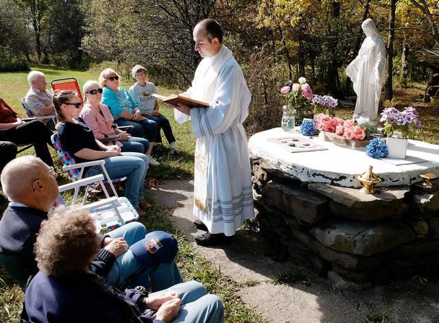 Father Daniel Ruiz-Sierra, parochial administrator of St. Anthony Church, speaks to parishioners before praying the rosary at Linda Benson's farm in Groton Oct. 7.