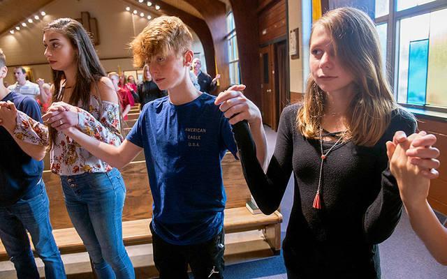 <p>Leah Sausa, Zachary Wake and Juliana Valone pray during the Life Teen Mass at St. Leo Church in Hilton Oct. 1.  </p>