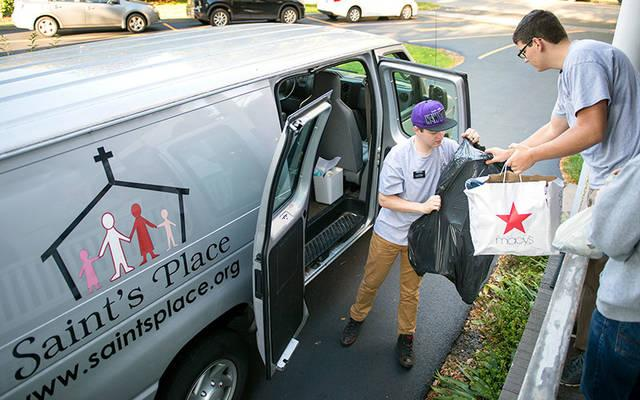 <p>Volunteers Tayson Hale (left) and Seth Clemens load a van with donated goods to be distributed at Saint's Place Oct. 18.  </p>