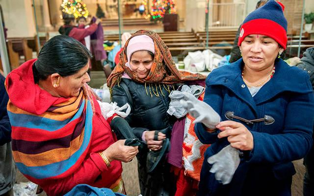 <p>Bhutanese women try on donated gloves Dec. 9, 2013, at Mary's Place, a refugee outreach center in Rochester.  </p>