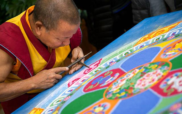 <p>The Venerable Tenzin Yignyen, a Tibetan Buddhist monk, creates a sand mandala Nov. 5 in the lobby of St. Ann's Community in Rochester as part of a weeklong series of events honoring grief.  (Courier photo by Jeff Witherow)   </p>