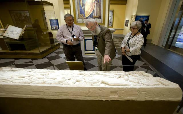 """<p>People stand near a bound book and biblical codices inside the """"History of the Bible"""" exhibit at the Museum of the Bible in Washington Nov. 15.  </p>"""