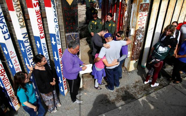 <p>U.S. Border Patrol agents open a single gate to allow families to hug and talk Nov. 18 along the U.S.-Mexico border in Tijuana, Mexico.  </p>