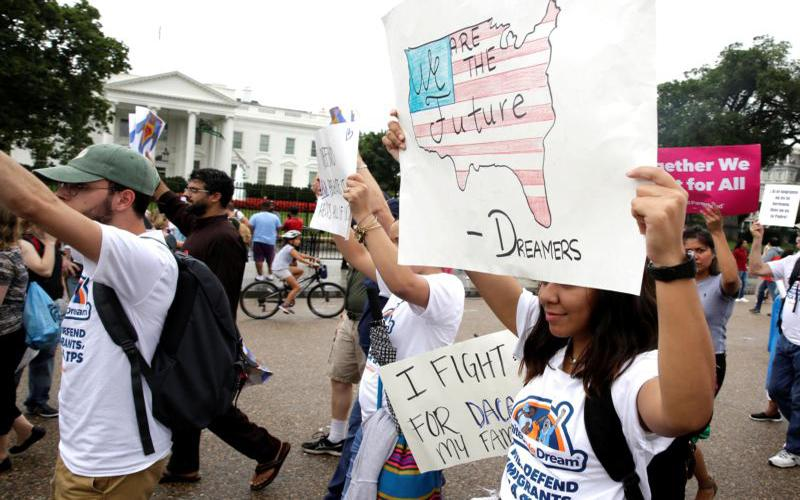 People march outside the White House Aug. 15 at a rally calling on President Donald Trump to protect the Deferred Action for Childhood Arrivals program, known as DACA.