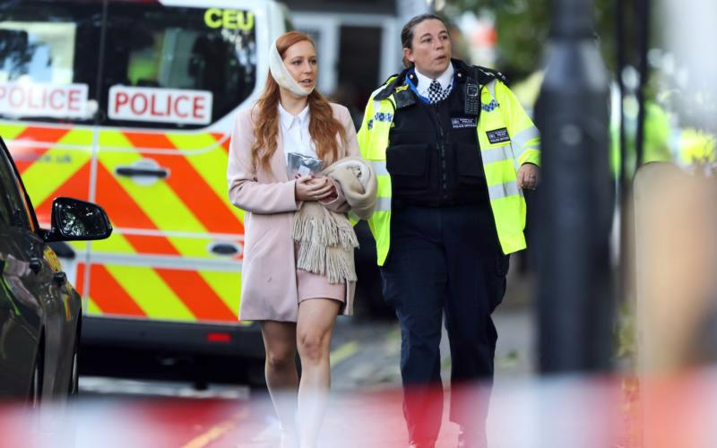 An injured woman is led away following a blast caused by an improvised explosive device on a London Underground train Sept. 15. The blast injured more than a dozen people and is being treated as terrorism by police investigators.
