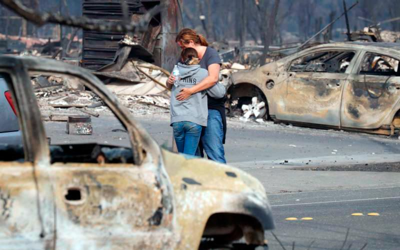 Residents embrace near the remains of destroyed homes Oct. 9 after wildfires in Santa Rosa, Calif. A series of deadly Northern California wildfires has killed at least 17 people, destroyed more than 2,000 buildings, including a section of Cardinal Newman High School in Santa Rosa.