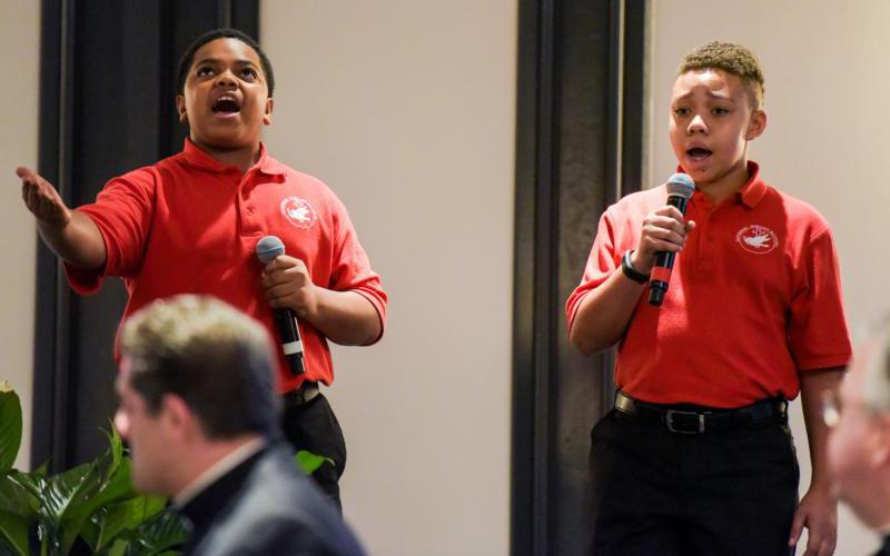 """Cardinal Shehan School choir members Kai Young and John Paige sing """"Rise Up"""" to open the Archdiocese of Baltimore's annual Partners in Excellence breakfast Sept. 6. The choir's viral video is closing in on 10 million views."""